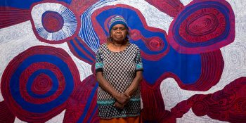 Betty Pumani with her work Antara 2017, appearing in the upcoming TARNANTHI festival in Adelaide. © Rhett Hammerton. Courtesy Mimili Maku Arts.