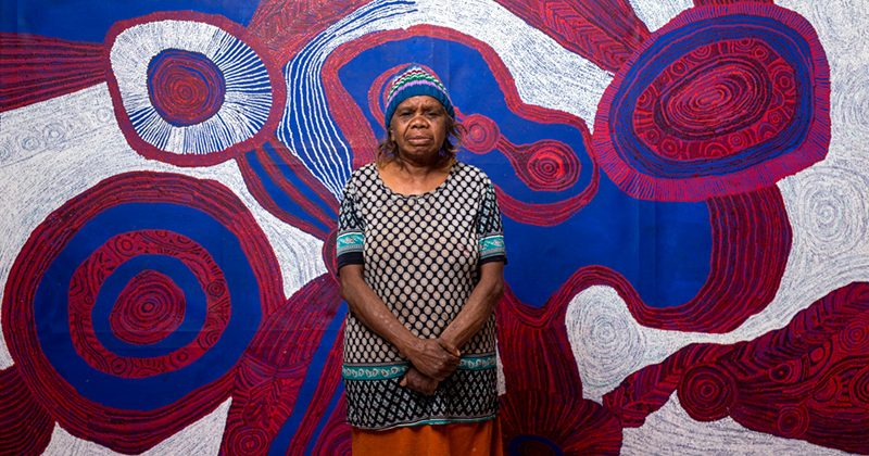 Betty Pumani with her work Antara 2017, appearing in the upcoming TARNANTHI festival in Adelaide. © Rhett Hammerton. Courtesy Mimili Maku Arts.