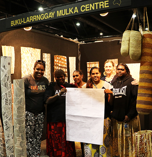 Copyright Agency's Trish Adjei with artists from the Buku-Larrnggay Mulka Centre holding the letter to government. Photograph by Gabrielle Sullivan.