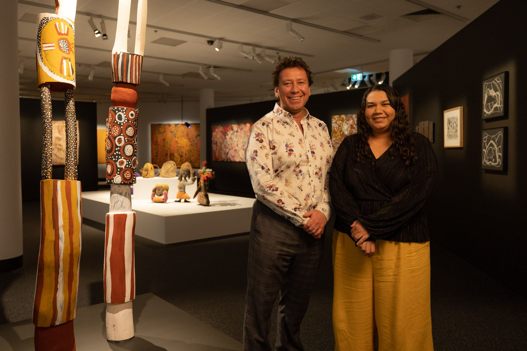 MAGNT Director Marcus Schutenko and MAGNT Curator of Aboriginal Art and Material Culture, Rebekah Raymond, standing alongside •Tutini (Pukumani poles) 2020 by artist Timothy Cook.